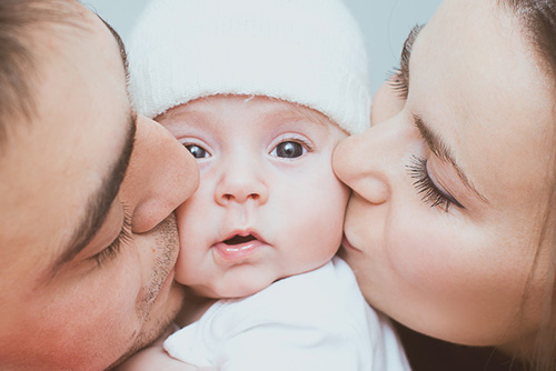 Mom & Dad Kissing Baby's Cheeks