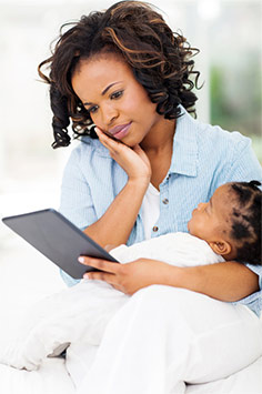 Mom on tablet holding sleeping baby